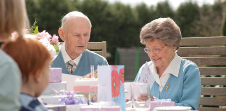 An elderly couple celebrating a birthday at home