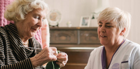 An elderly lady knitting with a Helping Hands care assistant